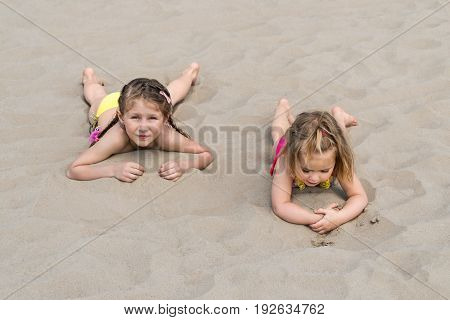 Two little girls are lying on their bellies on white sea sand