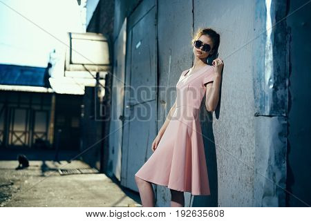Woman in glasses, woman in pink dress, woman on old wall background.