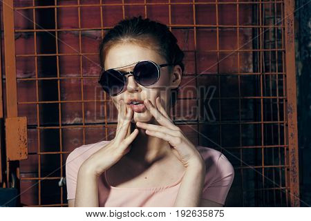 Woman in glasses, woman on old wall background.