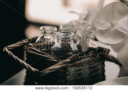 Glass Bottle in vintage Wicker basket. Decor box in loft interior. Flower blurred blackground. Vintage toning photo.