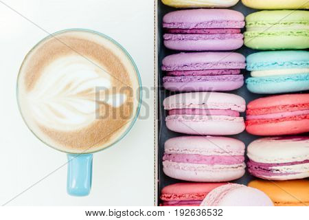 Morning Fresh French Macaron Cookies And Blue Cup Of Cappuccino On White Table