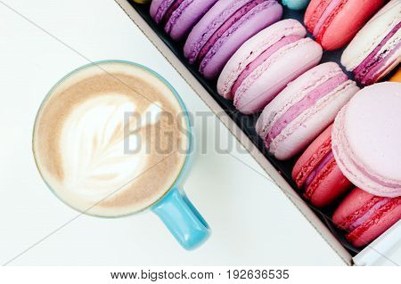 Fresh French Macaron Cookies And Blue Cup Of Cappuccino On White Table
