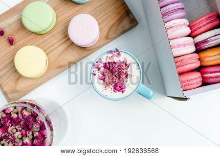 Tasty French Macarons And A Cup Of Cappuccino With Roses Petals