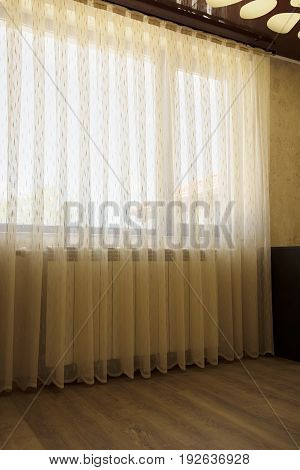 Window with beige sheer curtains interior decoration concept.