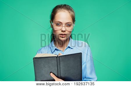 Woman with glasses, woman with a notepad, woman on a light background.