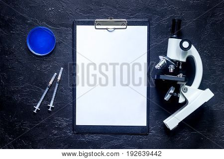 Medical tests. Work table of doctor witn microscope, syringe and ampoule on grey stone background top view.