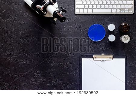 Medical tests. Work table of doctor witn microscope on grey stone background top view.