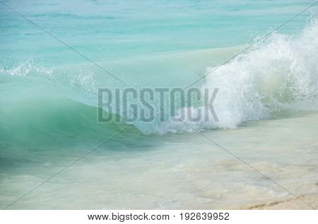 Glassy turquoise wave with white foam and splashes breaking along the beach on Zanzibar.