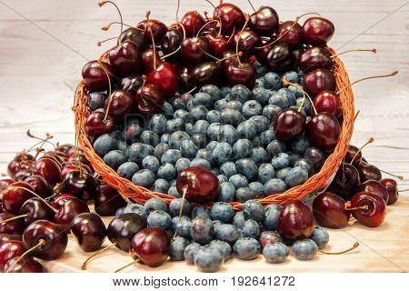 Fresh blueberries and fresh cherries in basket