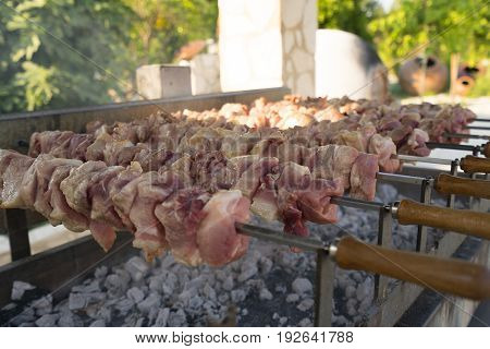 Shashlik being fried out-of-doors in a park on Cyprus island on summer sunny day close up shot