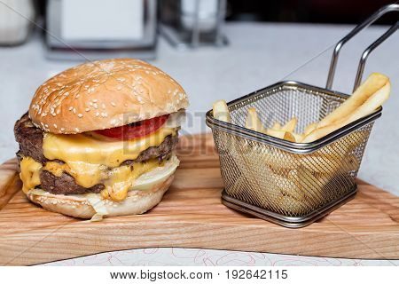 Burger with fresh tomato, cheese, meat and french fries.