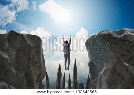 Businessman hanging on rope in danger concept