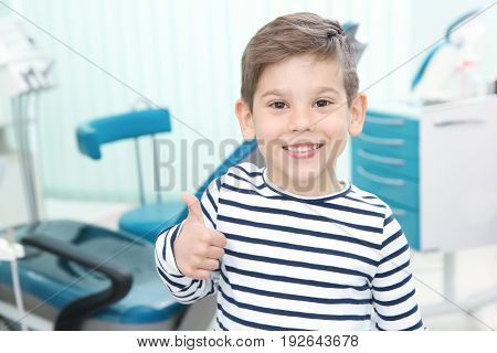 Cute little boy showing thumb up sign at dentist's office