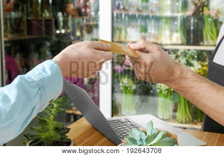 Young handsome florist receiving discount card from regular customer in flower shop, close up