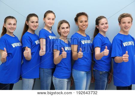 Group of young volunteers on color background