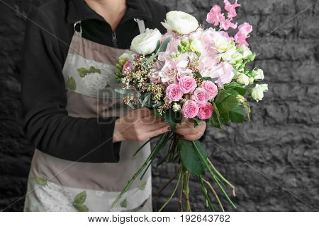 Female florist creating beautiful bouquet in flower shop on black brick wall background
