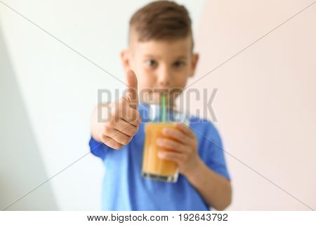 Cute little boy drinking juice and showing thumb up sign on light color background, closeup