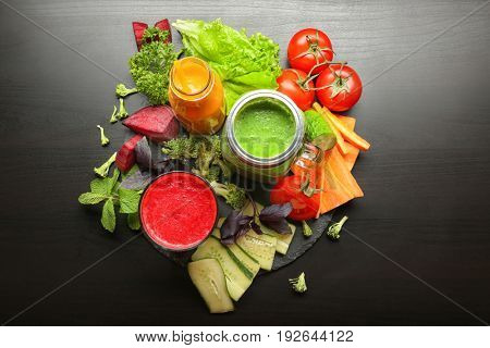 Fresh smoothies and vegetables on table