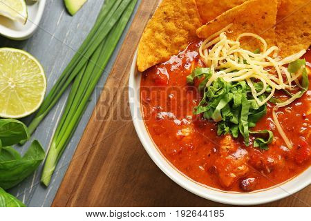 Bowl with delicious chili turkey and nachos on wooden board, closeup