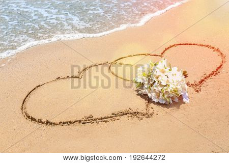 Bridal bouquet and hearts drawn on sand near water. Wedding concept