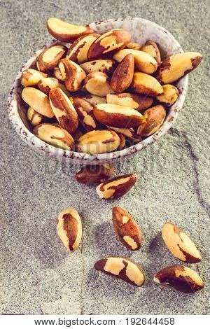 Bowl of peeled brazil nuts on stone background vertical. Closeup