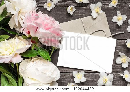 blank greeting card and envelope in frame of pink and white peonies and jasmine flowers over rustic wooden background. flat lay. top view with copy space. wedding invitation