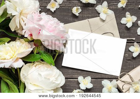 blank greeting card and envelope in frame of pink and white peonies and jasmine flowers with gift box over rustic wooden background. flat lay. top view with copy space
