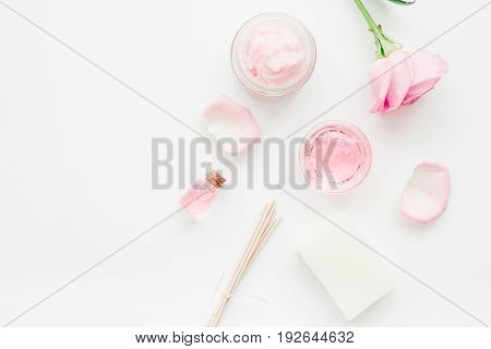 body treatment with rose flowers and cosmetic set on white desk background top view space for text