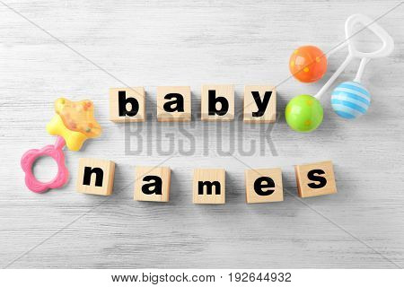 Cubes with words BABY NAMES and rattles on wooden background