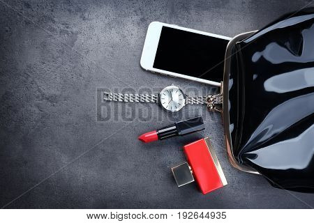 Accessories, cosmetics, perfume and phone near small bag on grey background
