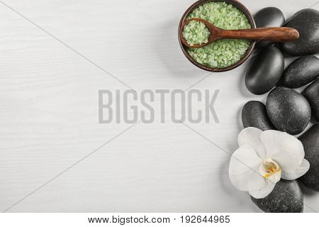 Spa stones with orchid flower and sea salt on light background