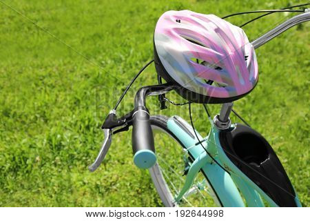 Bicycle stem and helmet on green grass background