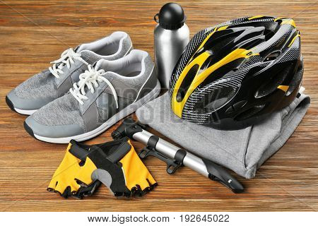 Bicycle accessories and biking clothes on wooden background
