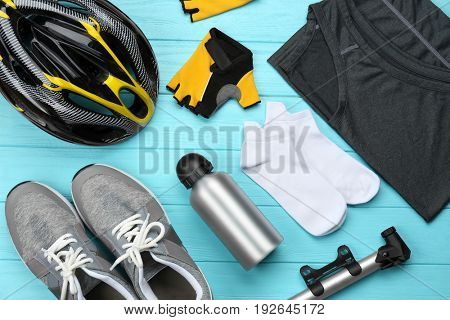 Bicycle accessories and biking clothes on color wooden background