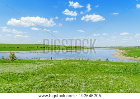 view of a river in green grass under a blue sky with clouds