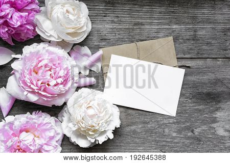 blank greeting card or wedding invitation and envelope with tender peonies flowers over rustic wooden background. mock up. flat lay. top view with copy space