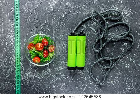 Healthy diet. Salad with fresh products and measuring tape on stone table top view copyspace.