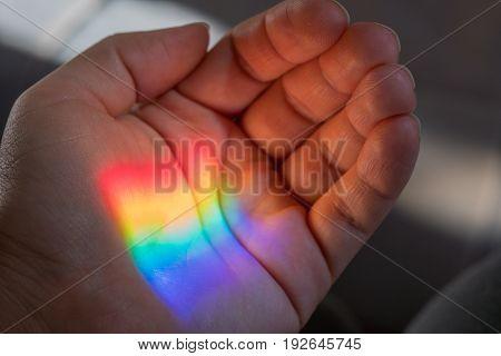 Rainbow sun shine light on a hand