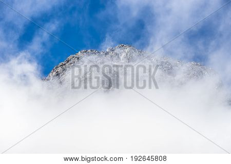 Fiordland National Park New Zealand - March 16 2017: Tall snow covered mountain peaks through white clouds near Monkey Creek valley under blue sky.