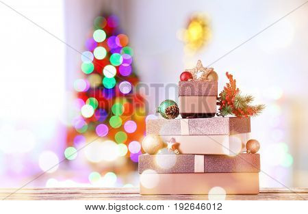 Beautiful Christmas gifts on table and blurred fir tree on background. Celebration of new year 2018