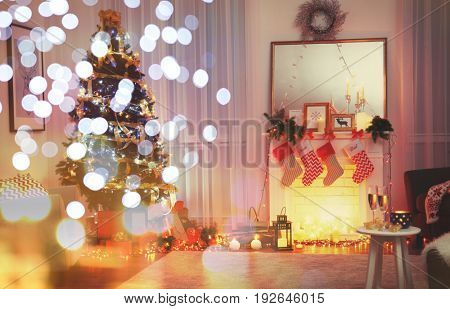 Interior of cozy living room decorated for Christmas. Festive and blurred lights design. Celebration of new year 2018