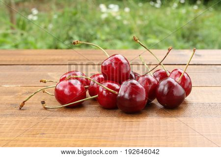 Ripe dark red cherries on a brown wooden table against green grass background