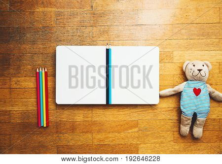 Child or baby play set with empty book or notepad colored pencils teddy bear. Back to school education concept. Kindergarten or preschool background.