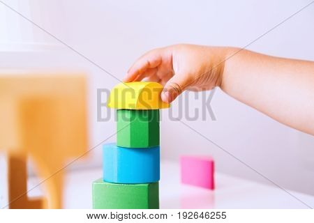 Baby playing and discovery with colorful toys at home close-up detail. Toddler plays with toy blocks and constructors. Early development learning and education of child or baby - background concept.