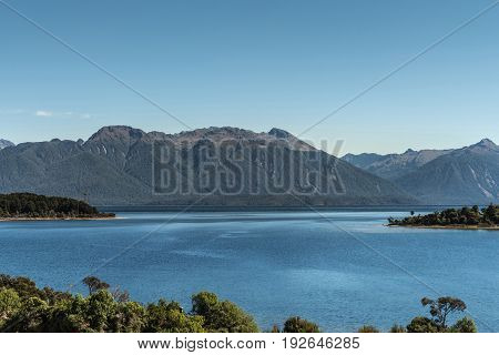 Te Anau New Zealand - March 16 2017: Looking over part of majestic lake Te Anau with dark blue water under light blue sky. Big mountainous slopes with forests and other green vegetation foreground.
