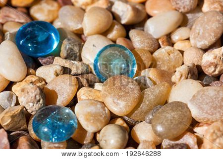 Three blue glass pebbles lay among small tumbled rocks of various origins in the sunshine.