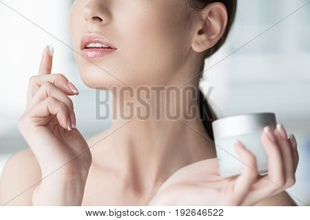 Close up of hands of young beautiful woman holding jar of cream in one hand and applying cream by finger on her skin