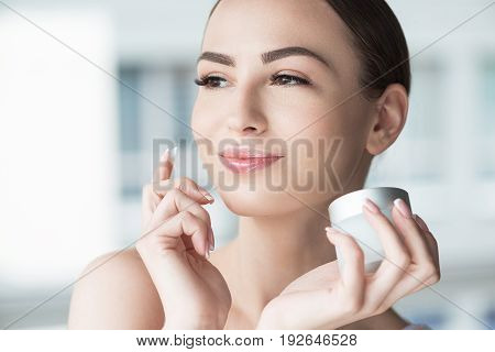 Portrait of jolly young attractive woman applying face cream. She is holding jar of cream in one hand and looking to distance with joy