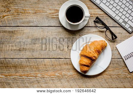 Businessman morning with keyboard, cup of coffee and croissant for lunch on wooden table background top view mockup
