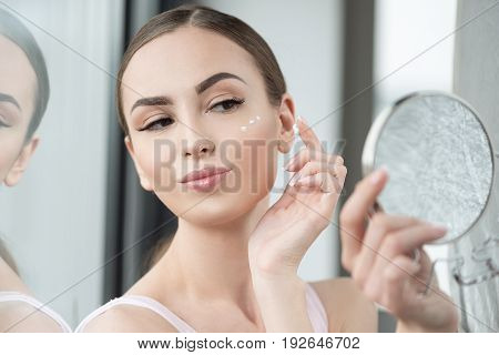 Portrait of jolly young girl putting dots of cream on her cheek. She is holding mirror in one hand and looking in it